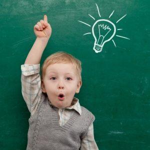 Bub vor einer Tafel, zeigt mit einer Hand nach oben. Auf der Tafel über seinem Kopf ist eine Glühbirne gezeichnet.